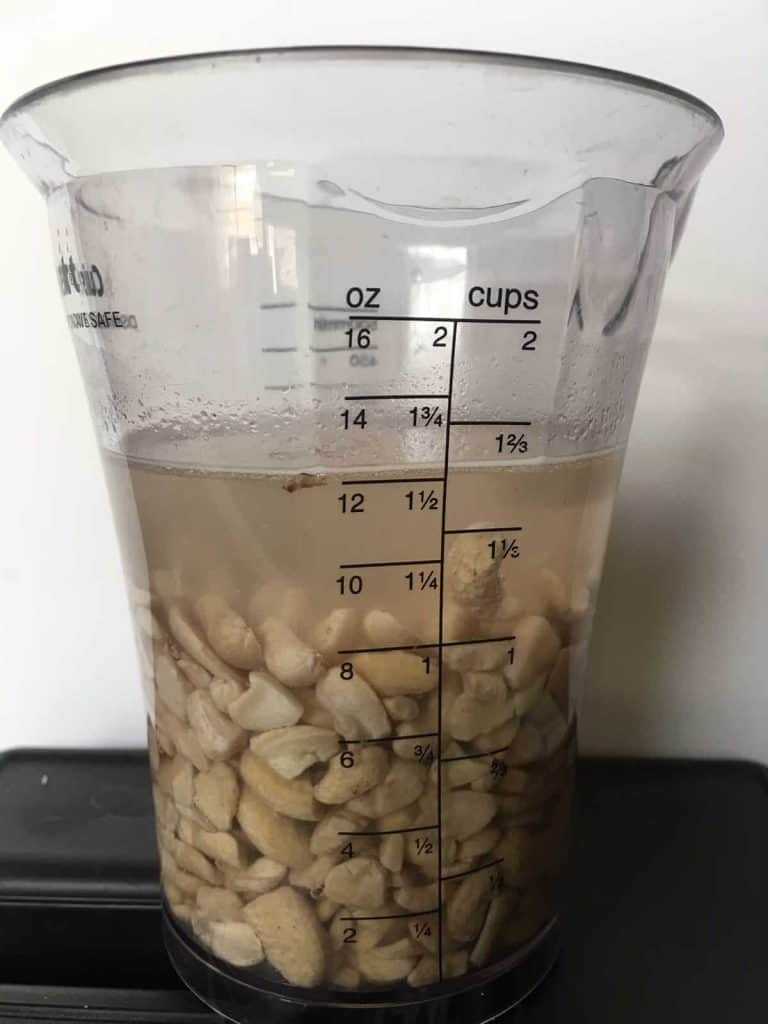 cashews soaking in measuring cup