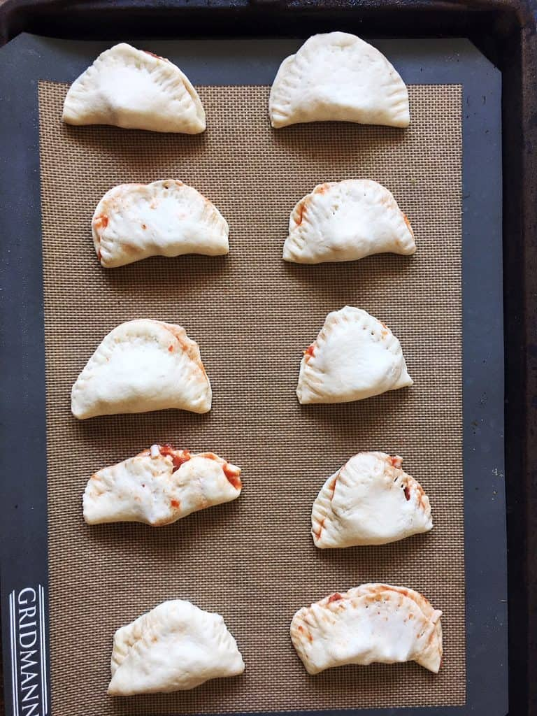 mini calzones on cookie sheet