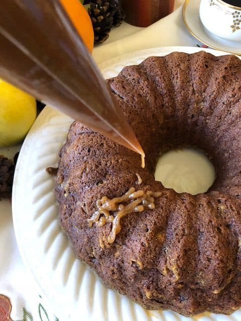 pumpkin bundt cake with caramel sauce drizzled on top with a pastry bag