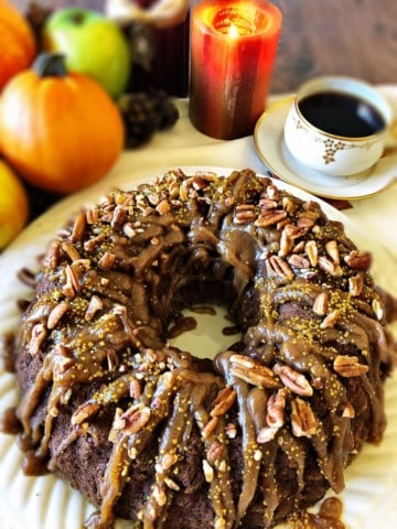 Pumpkin Bundt Cake with coffee, pumpkins, apples, and candle in background