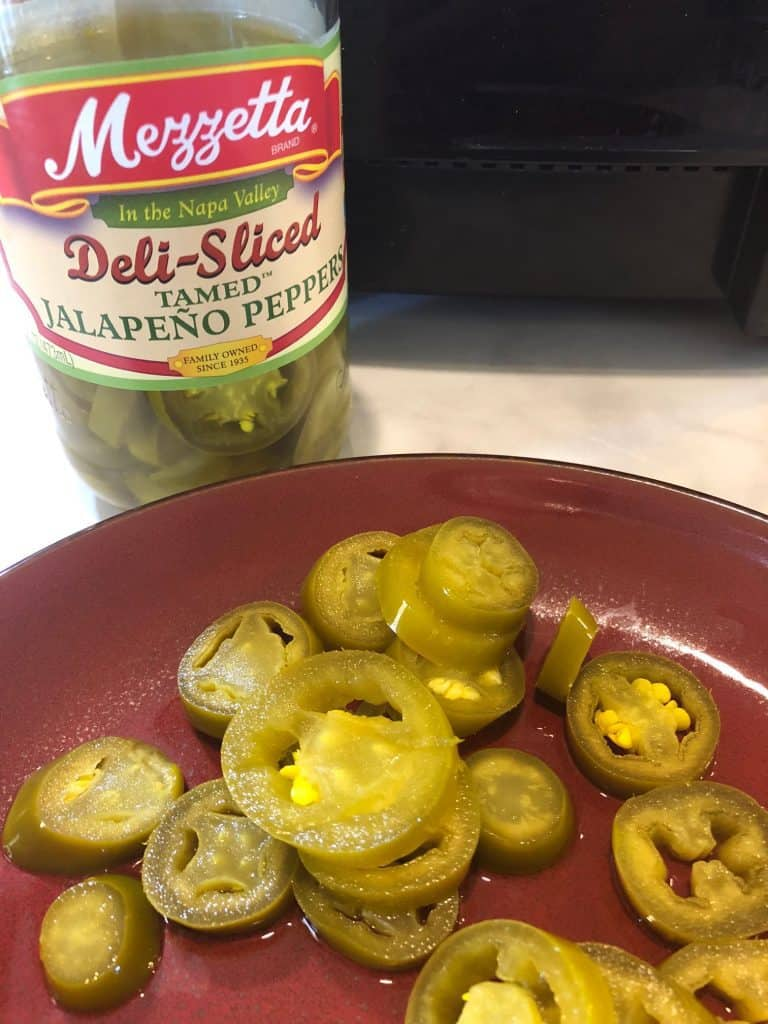 Jarred jalapenos on a red plate and in the bottle