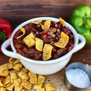 Chili in white bowl with corn chips and bell peppers