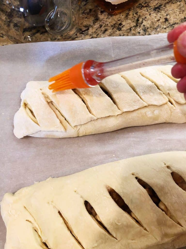 brushing liquid on apple cranberry puff pastry before cooking