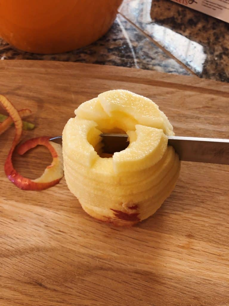 peeled and sliced apple being cut