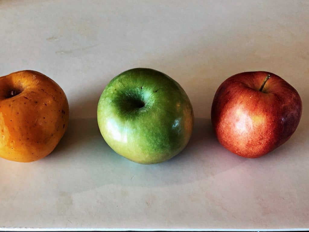 three apples - yellow, green, and red