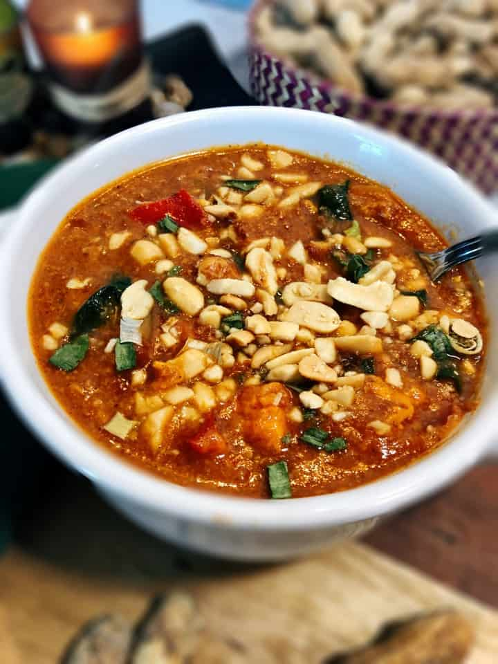 african peanut stew in white bowl with peanuts in background