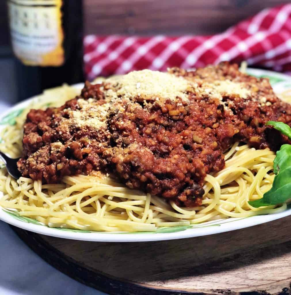 easy vegan Spaghetti on a plate with red checked cloth and bottle of wine in background