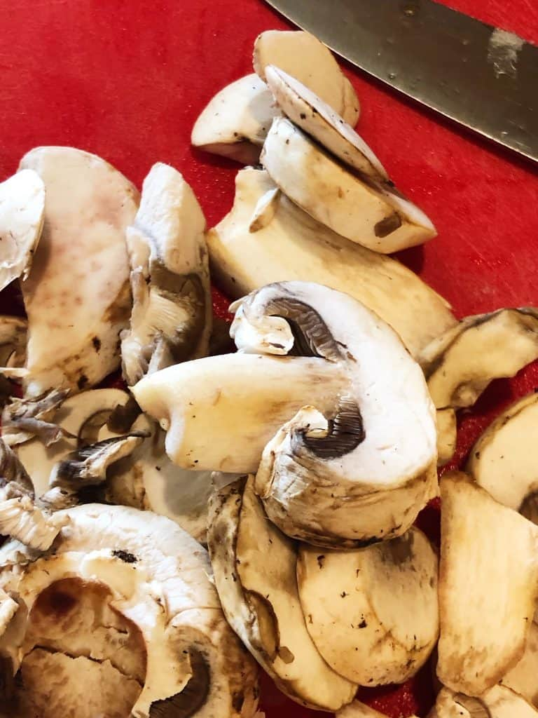 sliced white mushrooms on red cutting board with knife