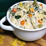 creamy vegetable pasta soup in white bowl with bow tie pasta in front