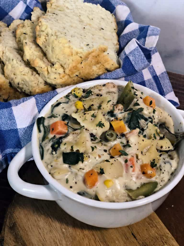 creamy vegetable pasta soup in white bowl with sliced bread on blue checkered napkin
