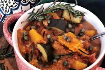 slow cooker butternut squash ratatouille in red bowl with green napkin and breadsticks