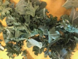 chopped kale on a yellow cutting board