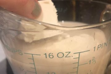 butter being placed in measuring cup with milk