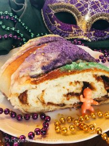 king cake with baby, beads, and mask