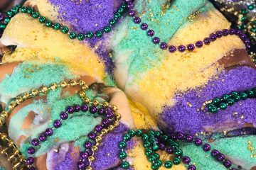 oval uncut king cake with beads and mask.