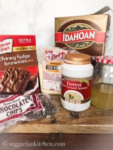 ingredients for vegan brownie hack: duncan hines brownie mix, chocolate chips, tahini, mashed potatoes in box, egg replacer