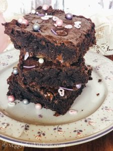 three brownies stacked on pink and purple flowered plate