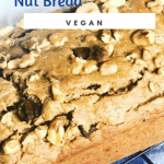 loaf of banana nut bread on rack with blue checkered cloth