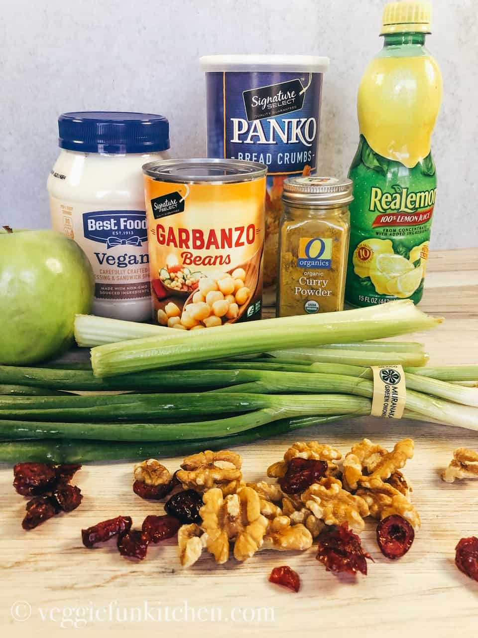 Ingredients you will need to make Curried Chickpea Salad including: vegan mayo, garbanzo beans, panko bread crumbs, lemon juice, granny smith apple, curry powder, celery, green onions, walnutsk, and dried cranberries.