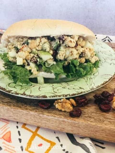 curried chickpea salad on bun on green plate on wooden tray