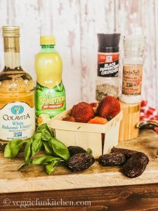 ingredients for strawberry balsamic dressing - vinegar, lemon juice, strawberries, basil, dates