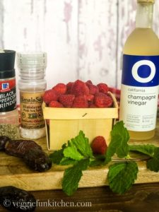 ingredients for raspberry mint vinaigrette dressing including champagne vinegar, raspberries, mint and medjool dates