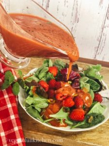 raspberry mint vinaigrette poured on berry salad with red checkered cloth