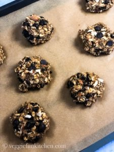 unbaked oatmeal cookies on parchment paper on pan