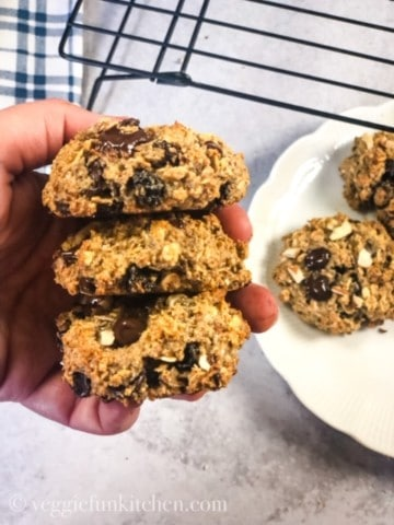 three oatmeal cookies held in hand with plated cookies on a white plate and black cooling rack in the background