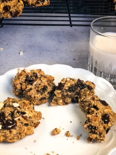 oatmeal cookies on white plate with glass of almond milk and black rack in background