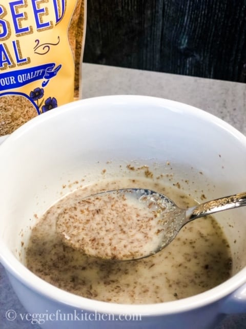 flax meal and almond milk in a white bowl with spoon