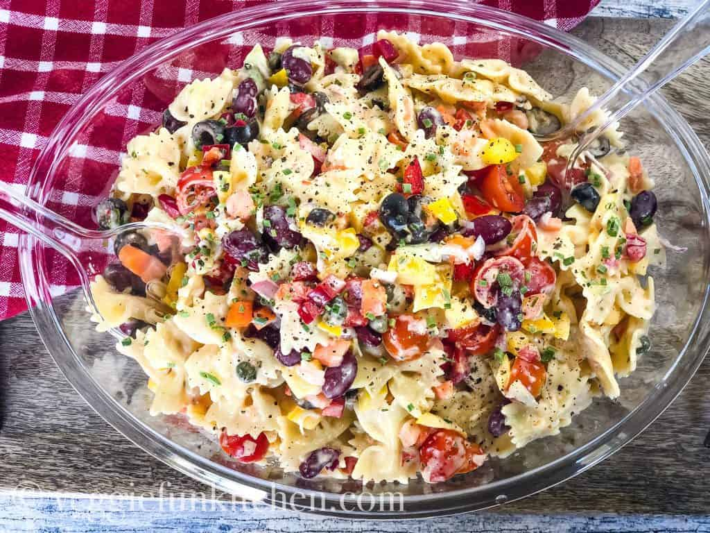 italian Pasta Salad in clear bowl with red checked cloth