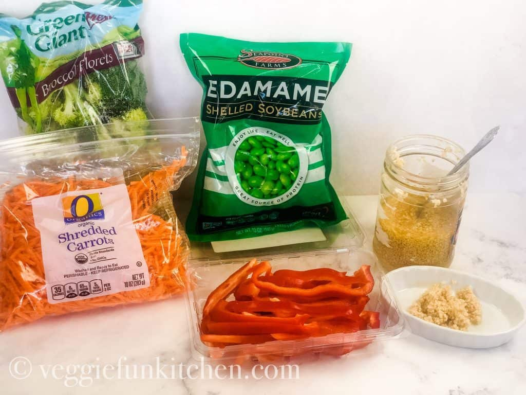vegetable ingredients for asian noodle stir fry including broccoli, shredded carrots, red pepper slices, edamame, and minced garlic