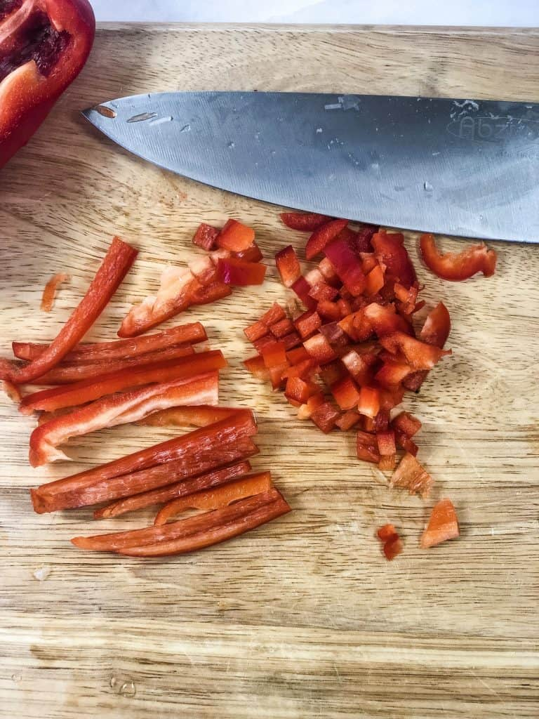 diced red bell peppers on wooden board with knife