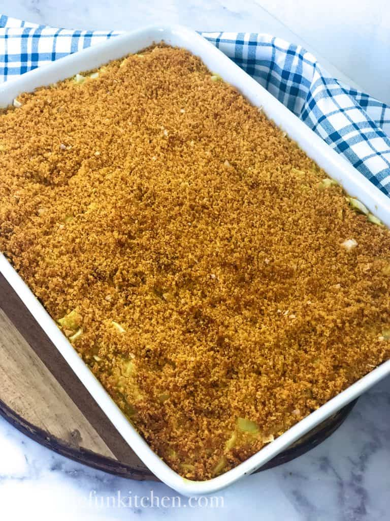 vegan funeral potatoes in white casserole dish with blue checked napkin