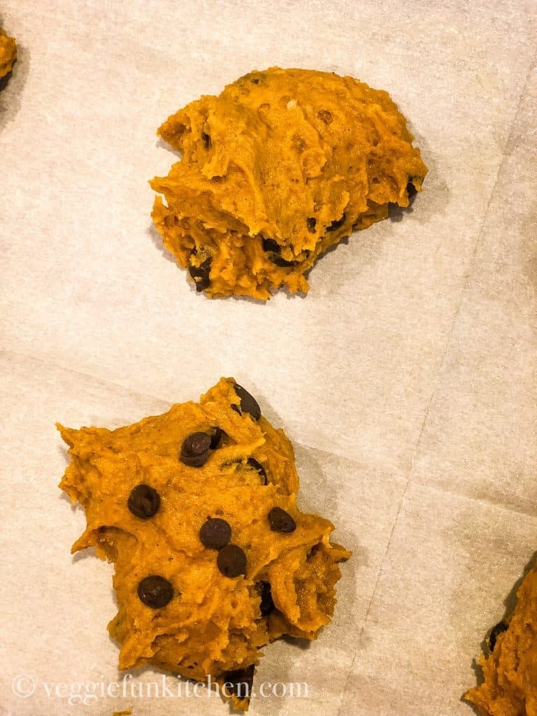 two pumpkin cookies on the cookie sheet. One with extra chocolate chips on top and one without.