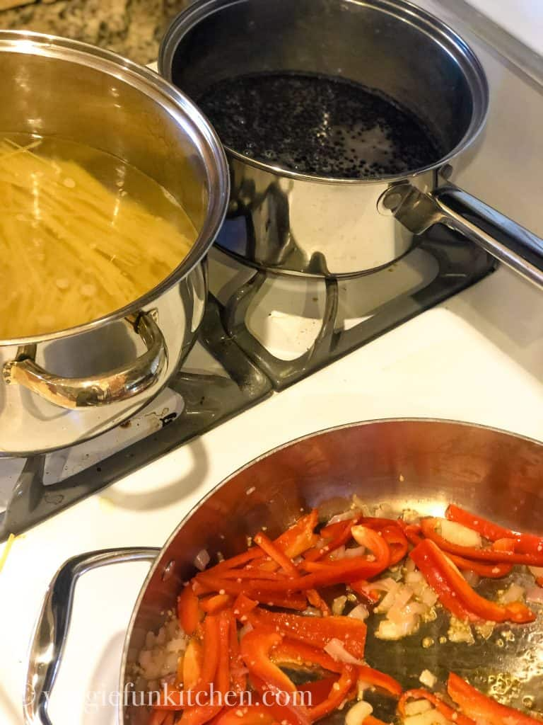 three pans on stovetop with pasta, lentils, and bell peppers