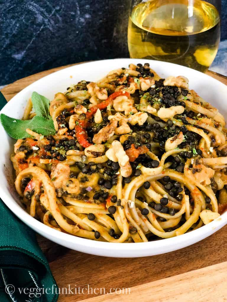 pasta with pumpkin sage sauce in white bowl with wine in glass