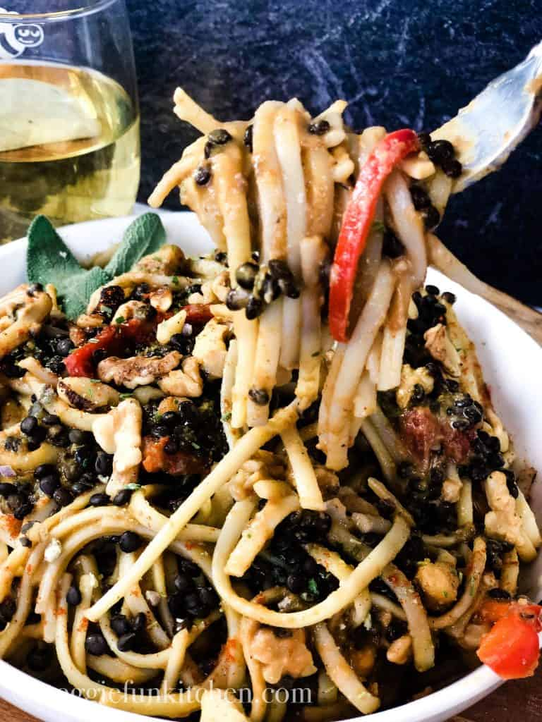 pasta with pumpkin sage sauce on fork and in white bowl with wine in glass