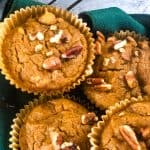 four muffins in a basket with green napkin
