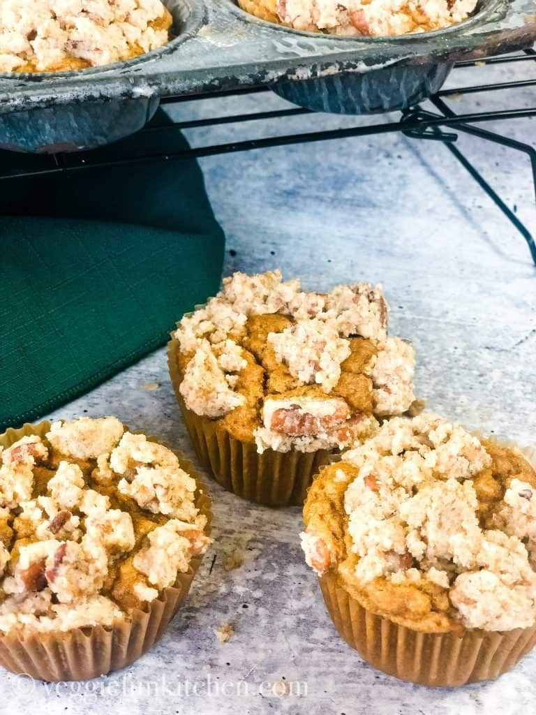 three pumpkin muffins on the counter and two on the rack above.