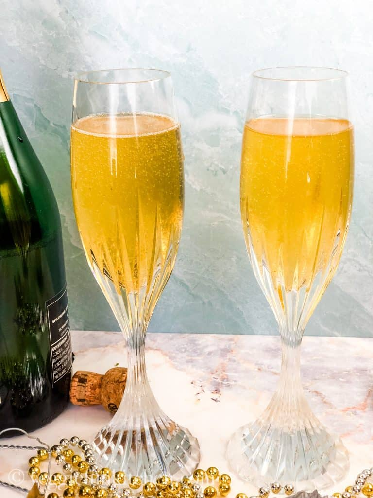two champagne flutes with champagne and white balsamic reduction