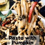 pasta with pumpkin sage sauce on fork in white bowl with wine in glass