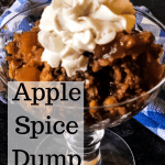 Apple spice dump cake in crystal goblet topped with whipped cream with blue checkered napkin in background. Text overly