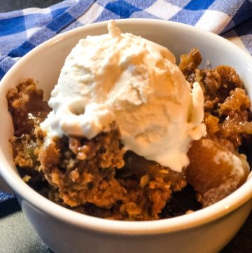 Apple spice dump cake in white bowl topped with ice cream with blue checkered napkin in background.