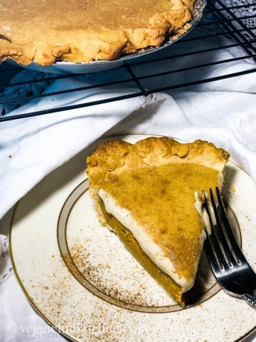 pumpkin pie with cashew cream on white and gold plate with pie on rack in background.