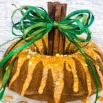 Pumpkin bundt cake on white plate with cinnamon stick and green rafia stem