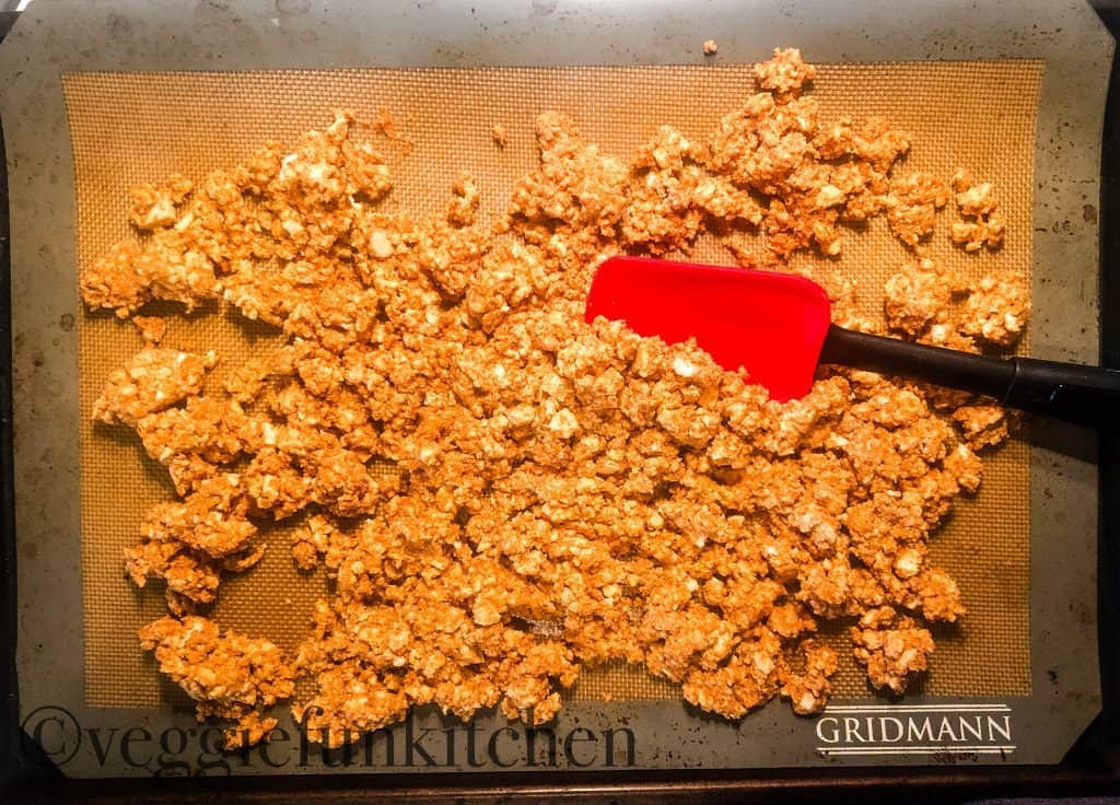 tofu bacon crumbles on matt being broken up with red spatula