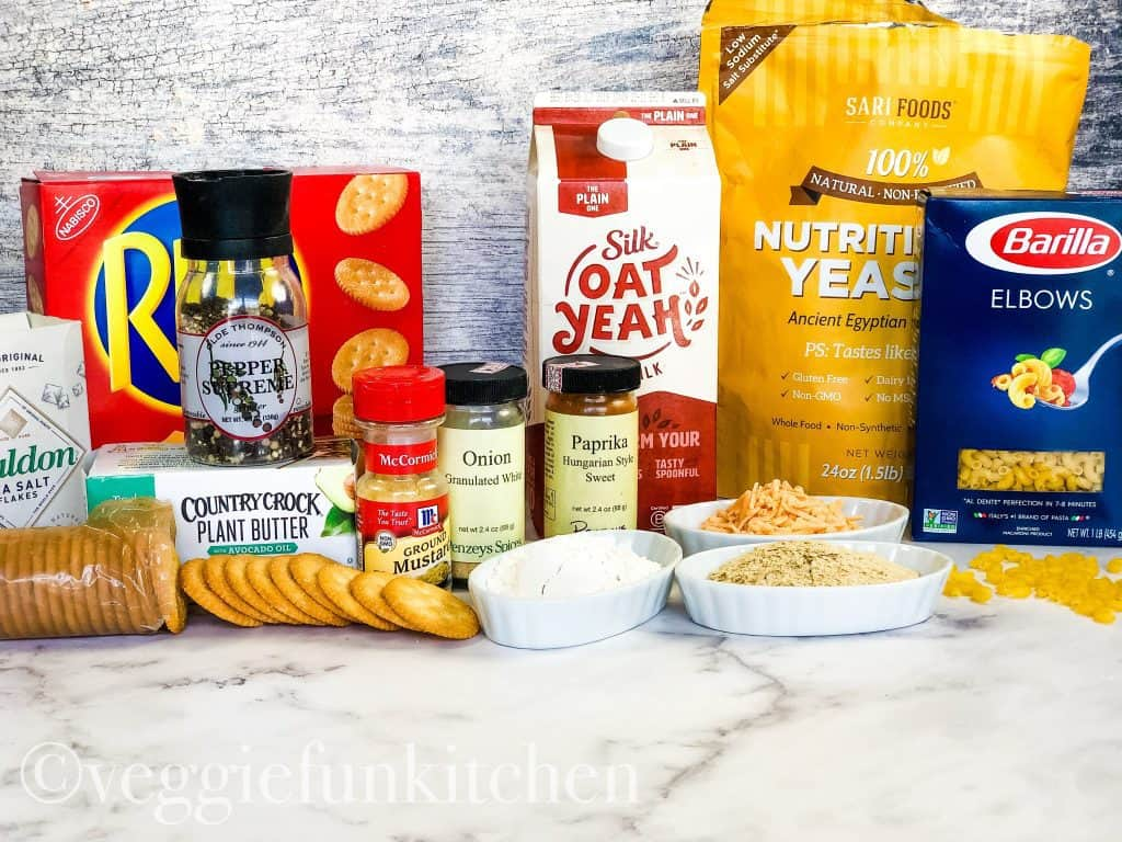 ingredients for vegan baked mac and cheese including ritz crackers, vegan butter, plant milk, nutritional yeast, and macaroni