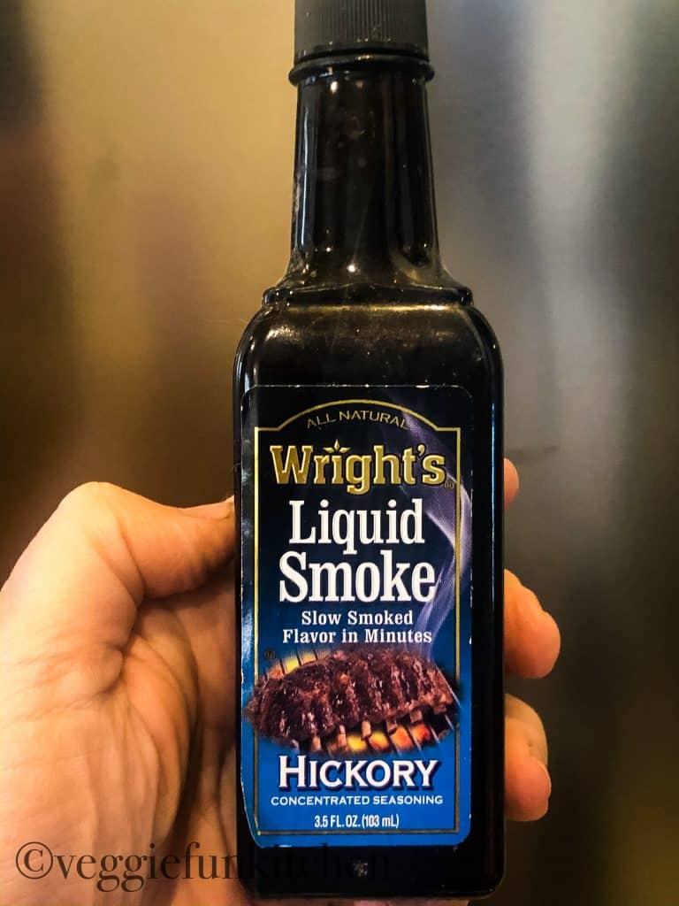 liquid smoke in bottle held in hand